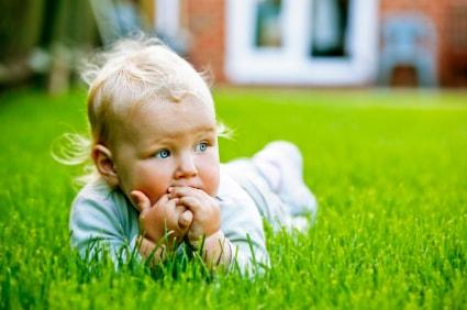 Bébé dans l'herbe qui se mange les doigts avant d'aller chez l'ostéopathe