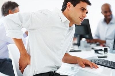 Homme assis à son bureau qui se tient le dos qui parait avoir mal