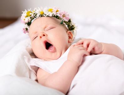 Un bébé qui baille dans un lit après avoir consulté un ostéopathe