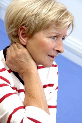 Femme qui se tient le cou après une entorse cervicale et qui consulte un ostéopathe